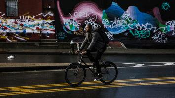 black man riding bicycle on road