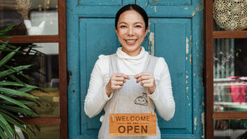 cafe owner showing welcome we are open inscription