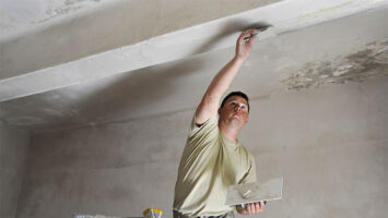 man applies plaster to ceiling