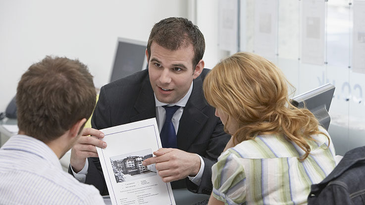 real estate agent presenting a property to his clients