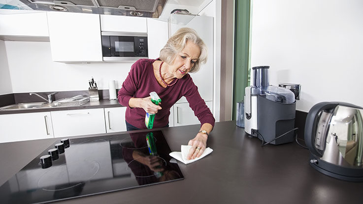 Senior woman cleaning kitchen counter