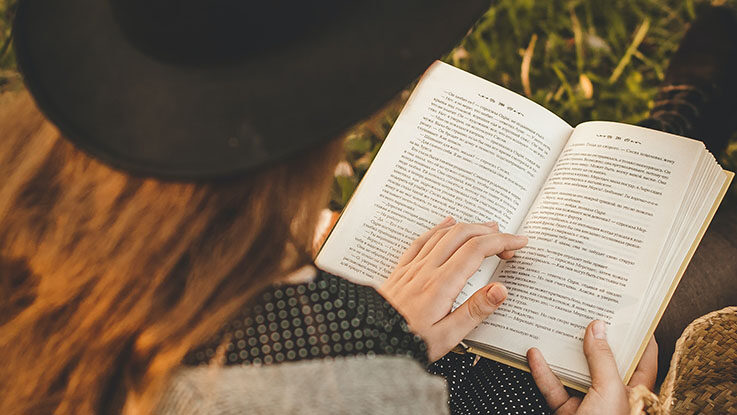 young woman reading a book outdoor